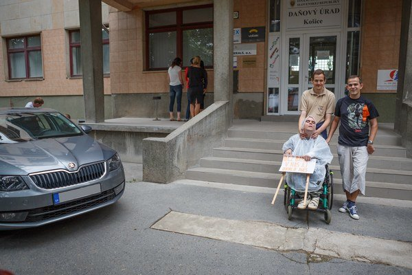"""Daňový úrad. Keď si chce vozičkár niečo vybaviť, musia mu po schodoch pomôcť minimálne dvaja ľudia. Tu mali """"šťastie"""" na arogantne zaparkované auto, ktoré len ledva vedeli obísť."""