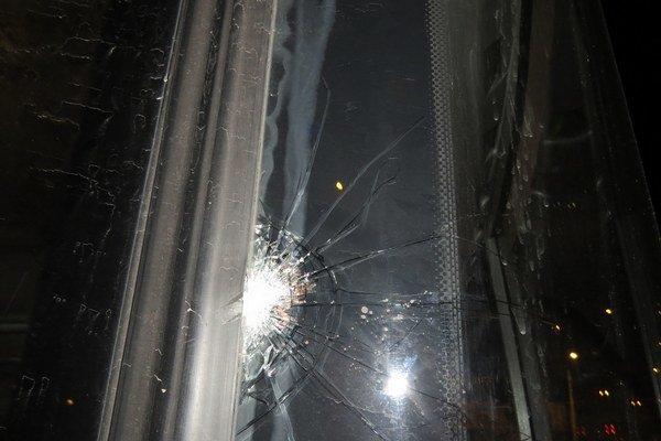 Rozbité sklo autobusu. Dostalo zásah dlažobnou kockou.