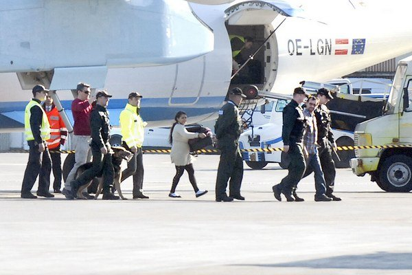 Medzi cestujúcimi v sprievode polície kráča odsúdený.