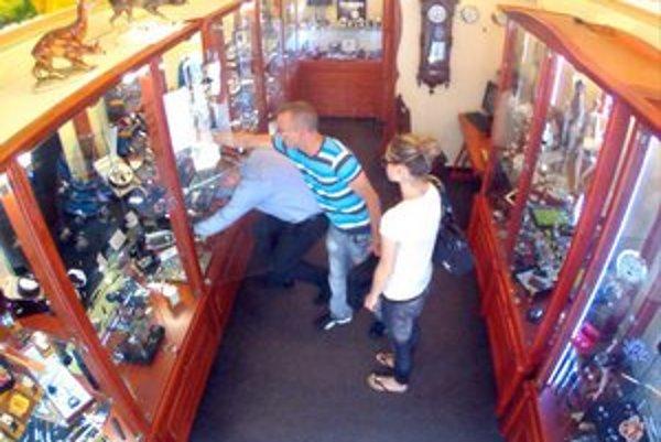 Krádež. Páchateľ sa nahol cez predavača a hodinky rýchlo vytiahol z vitríny.