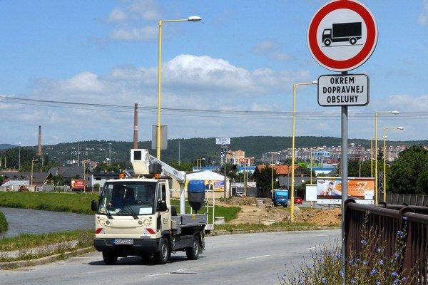 Medzi domami a riekou. Po Severnom nábreží chodia autobusy a osobné aj nákladné autá.