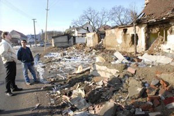 Starosta s obyvateľom Badžom obzerajú ruiny jedného z domov.