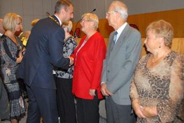 Dôchodcovia. Dostali spomienkové ocenenie a kvietok.