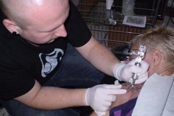 Pepo práve tetuje ornament na rameno zákazníčky.