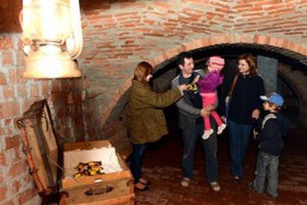 Vávštevníci v solivarskom múzeu počas prehliadky strašidelnej bane pri truhlici pokladov so sladkosťami.