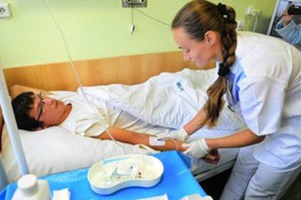 Silvia Odelgová z oddelenia urológie bezpečnostnou kanylou napicháva pacientovu žilu na napojenie infúzneho roztoku.