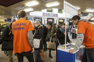 Brigádnici v oranžových tričkách pomáhajú cestujúcimna stanici s registráciou.