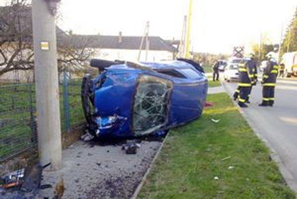 Prevrátené auto. Najprv narazilo do telefónneho stĺpa a vytrhlo ho.