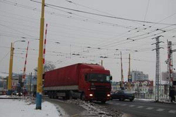 Železničné priecestie. Pre stojaci vlak na stanici Prešov-mesto sa na ulici vytvárajú kolóny, keď sú spustené závory.
