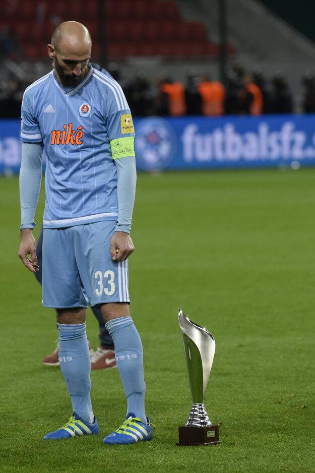 Róbert Vittek sa pozerá na pohár za druhé miesto. Slovanu v minulej sezóne ušlo prvenstvo v Slovnaft Cupe tesne.