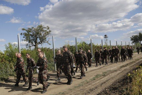 Maďarskí vojaci kráčajú okolo plota pri hranici.