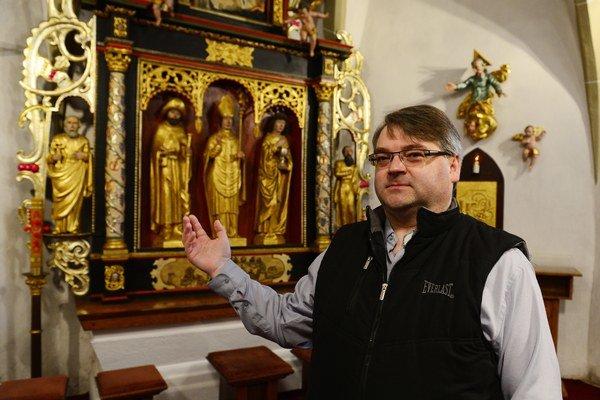 Na snímke pred oltárom s plastikami z dielne majstra Pavla z Levoče je miestny farár Marek Senderák.