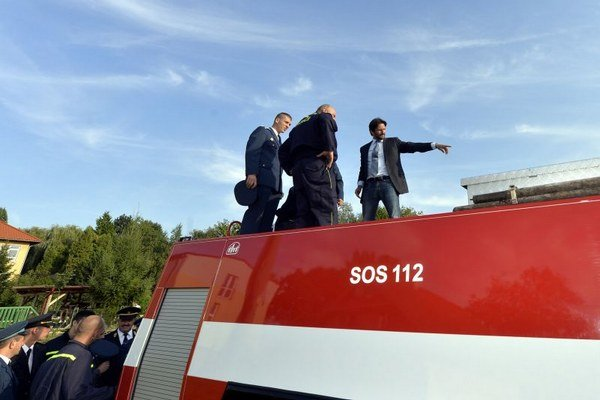 Robert Kaliňák (vpravo) ukazuje dobrovoľným hasičom nadstavbu zrenovovanej Tatry T 148.