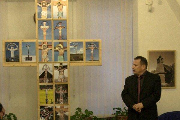 Milan Malast na vernisáži. Kríž z fotografií krížov, ktoré fotil pri drevených kostolíkoch, je súčasťou výstavy.