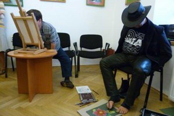 Vernisáž výstavy. Ukážku maľovania ústami a nohami predviedli poľskí umelci Stanisław Kmiecik a Mikolaj Kastelik.