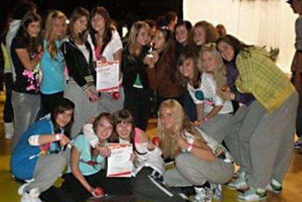 Kto tancuje v Prodigy-B. Je to Andrea Kováčová, Nikola Čurilová, Zuzana Jablonská, Viktória Kováčová, Lenka Kuncová, Alexandra Bálintová, Anna Bangová, Luana Kundrátová, Zuzana Vatahová, Bibiána Sotáková, Simona Andiľová a Dominika Baníková.