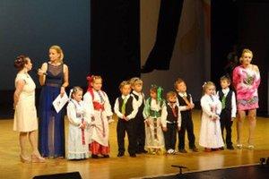 Škôlkari z Tužiny na pódiu s učiteľkami a Adelou Banášovou.