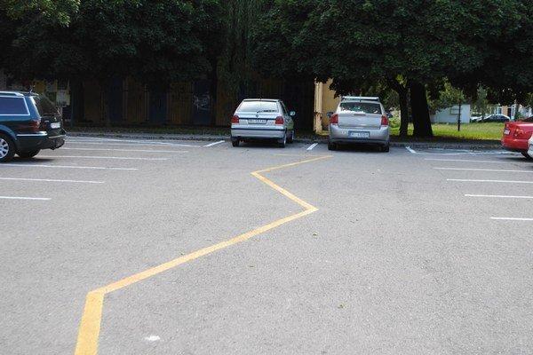 Parkovisko. Žltá kľukatá čiara v strede parkoviska vyznačuje priestor, kde je zakázané státie.