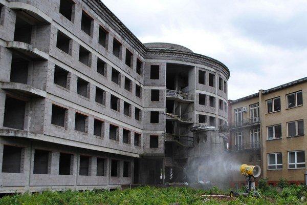 Nasadili vodné delá. Päťposchodový monoblok búrajú pásovým rýpadlom s prídavnými hydraulickými kliešťami a búracím kladivom. Prašnosť v areáli  nemocnice minimalizujú vodnými delami.