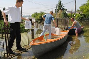 Netradičný prevoz urny po zaplavenej dedine na člne v Petrikovciach.