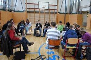 Vyučovanie v telocvični. Žiaci majú hodinu pod basketbalovými košmi. V triedach cítiť syntetické farby.