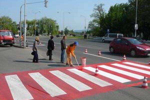 Cesty v meste. Vodiči a poslanci na natieranie vodorovného značenia v čase dopravnej špičky hromžia.