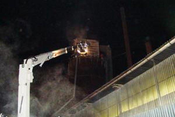 Požiar zásobníka. Hasili ho pomocou vysokozdvižnej plošiny. Pohyb hasičov komplikoval klzký povrch na sile.