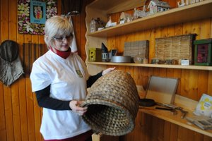 Magdaléna Galliková. V ruke drží úľ, ktorý používali starí otcovia.