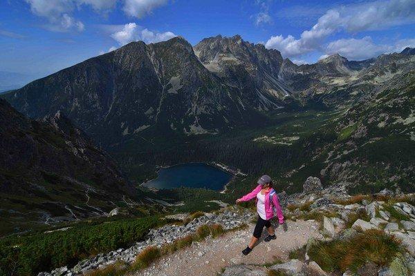 Turistka schádza po chodníku zo sedla pod Ostrvou (1 980 metrov nad morom) nad Popradským plesom v Mengusovskej doline.
