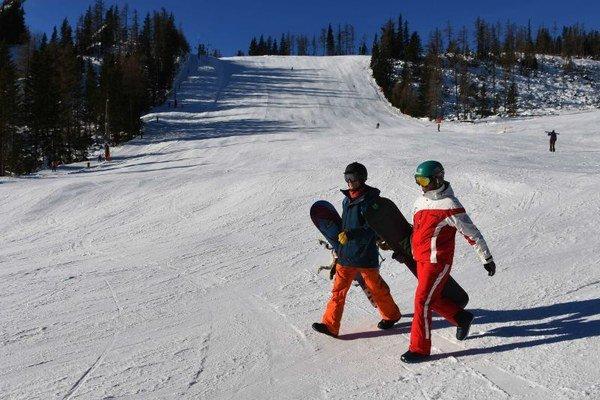 Na snímke snoubordisti kráčajú po zjazdovke v lyžiarskom stredisku na Štrbskom Plese počas otvorenia lyžiarskej sezóny vo Vysokých Tatrách.