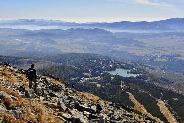 Turista obdivuje výhľad na Štrbské pleso a Podtatranskú kotlinu z vrcholu Predného Soliska.