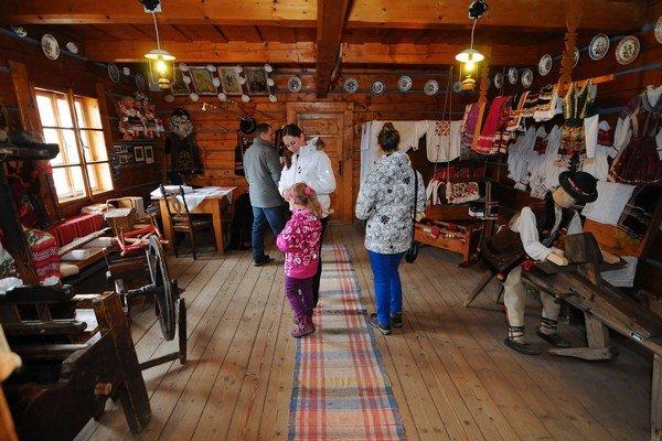 Rodinka turistov si prezerá interiér tradične zariadenej ždiarskej izby v Múzeum Ždiarsky dom.