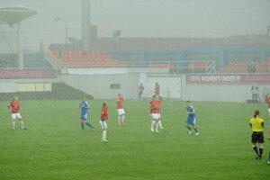 Futbalistky Nórska (červené dresy)a Slovenska (modré dresy) počas silného lejaku.
