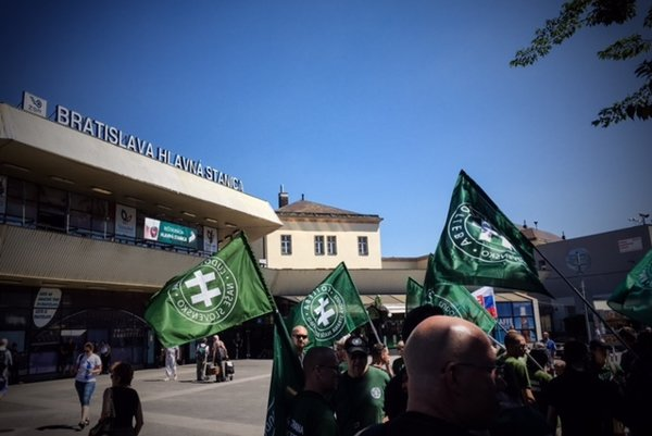 Kotlebovci s vlajkami ĽS-NS pred bratislavskou hlavnou stanicou.