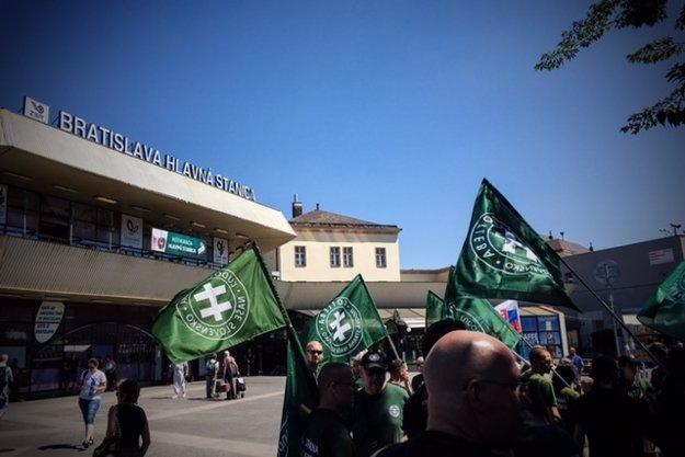 Kotlebovci s vlajkami ĽSNS pred bratislavskou hlavnou stanicou.