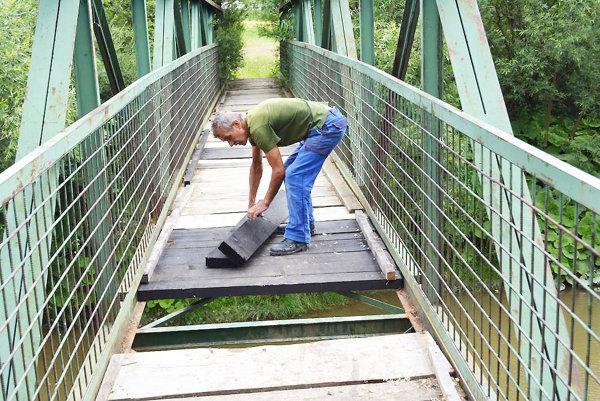Pracovník miestnej prevádzky opravuje poškodený most.
