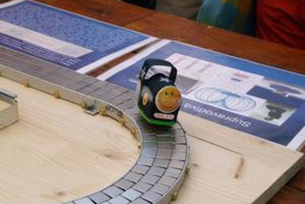 Košický levitujúci vláčik. Supravodivý kotúčik na spodku vláčika sa vznáša nad magnetickou dráhou.