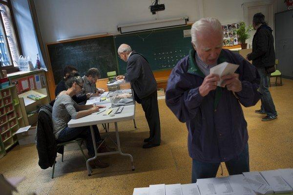 Ľudia vo volebných okrskoch.