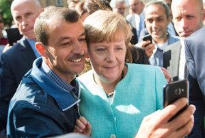 Angela Merkelová s jedným z utečencov v azylovom centre v Berlíne, 10. seprtembra 2015.