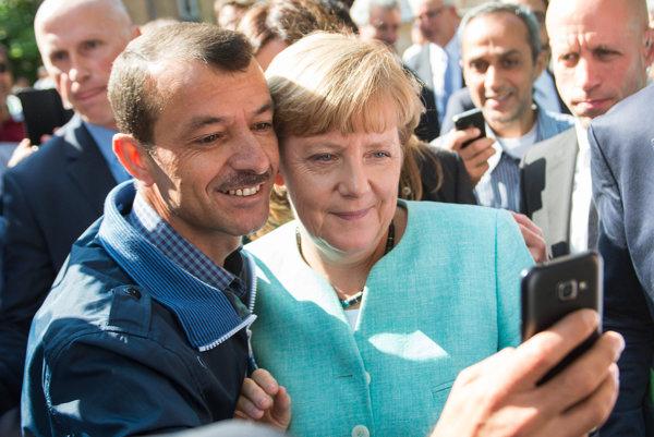 Angela Merkelová s jedným z utečencov v azylovom centre v Berlíne.