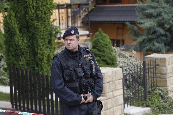 Policajt hliadkuje pred miestom vraždy 23. mája 2013 v Brne.