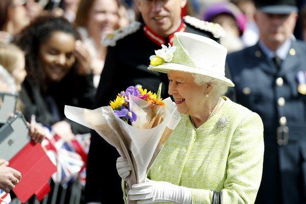 Britská kráľovná dostáva kvety od svojich fanúšikov počas osláv svojich 90. narodenín.