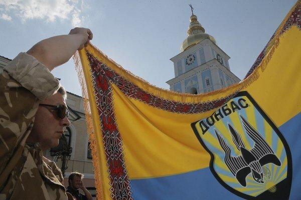 """Dôstojník z dobrovoľníckeho práporu """"Donbas"""" drží bojovú zástavu."""