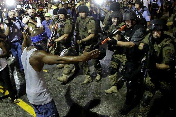 Policajti zatýkajú muža počas demonštrácií proti vražde 18-ročného černošského mladíka Michaela Browna.