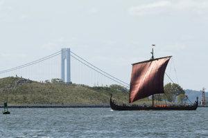Nórska vikingská loď Draken Harald Haarfagre sa plaví v ústí rieky Hudson s mostom Verrazano v New Yorku v pozadí.