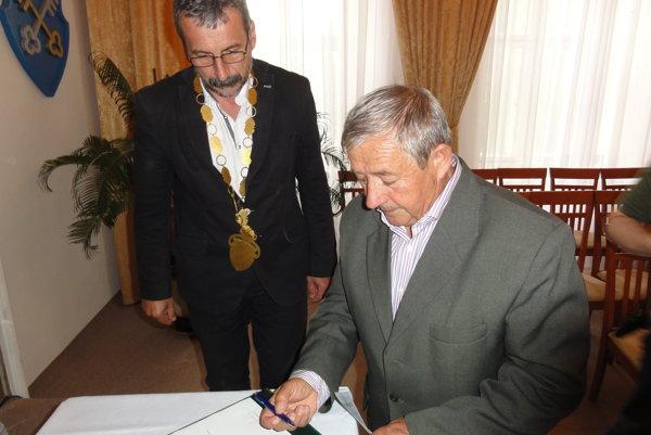 Marián Tomajko skladá poslanecký sľub. V pozadí je primátor Dušan Husár.