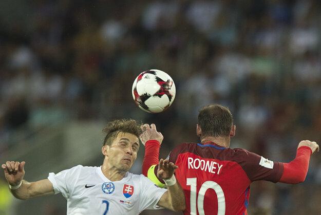 Wayne Rooney (vpravo) zvádza hlavičkový súboj s Petrom Pekaríkom.