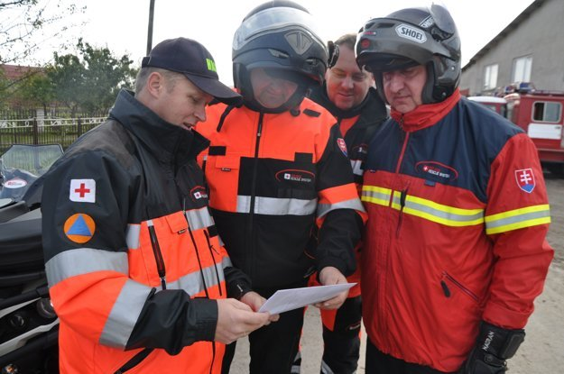 Členovia Orava rescue system prezerajú mapu územia, kde pôjdu hľadať.