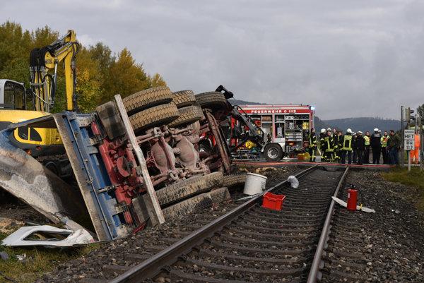 Vrak nákladného auta pri železničných koľajach.