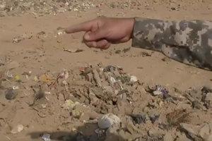 Na snímke z videa iracký policajt ukazuje smerom k masovému hrobu v meste Hamám al-Alíl.